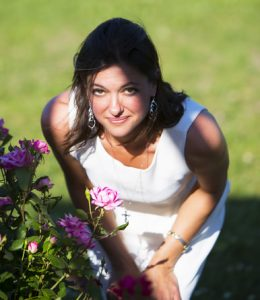Woman with brown hair and white dress stooping over to smell some flowers