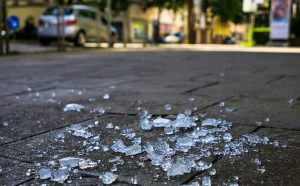 Shards of glass on pavement with street scene in background