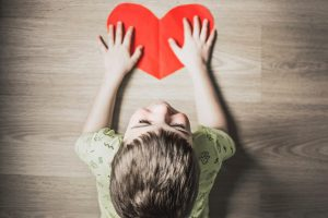 Boy with hands on a  top of a red paper heart