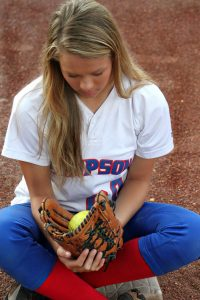"""I caught """"Hope!"""" Teenager sitting Indian style on dirt field cradling a glove with a ball in it."""