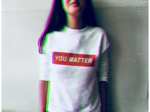 "woman with brown shoulder length hair wearing a white tshirt with a red block of print that says ""you matter"""