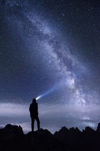 Man with a spotlight hat looking up at a galaxy, nite scene