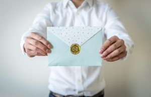 "Man holding out a light blue envelope that has a gold circle sticker on the back that has ""Happy Mail"" embossed on it."