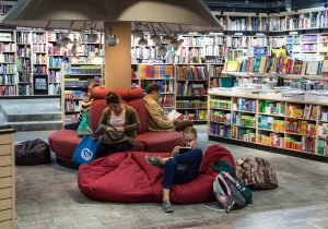 Comfortably browse our online store-Look over our products and site. Bring a friend! (Image is of a bookstore with plenty of soft-seating and bean bags. Multiple people in photo.